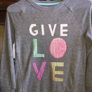 Gray sweater with sequenced writing give love.